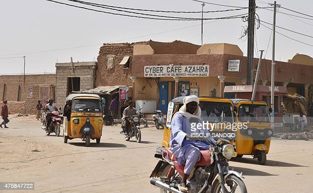 People ride motorcycles and drive vehicles in a neighbourhood of the city of Agadez northern Niger on May 30 2015 AFP PHOTO / ISSOUF SANOGO