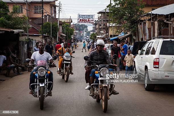 People ride motorcycles in a street of Freetown on October 4 2014 The Ebola epidemic has infected more than 6200 people in West Africa since late...