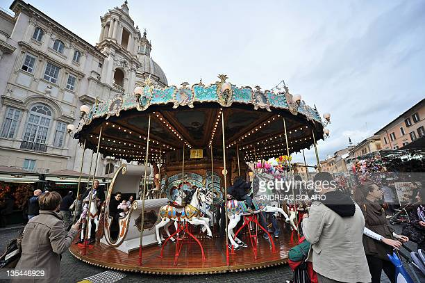 People ride on a carousel installed in the Piazza Navona in Rome on December 10 2011 as part of the christmas market The Italian government expects...