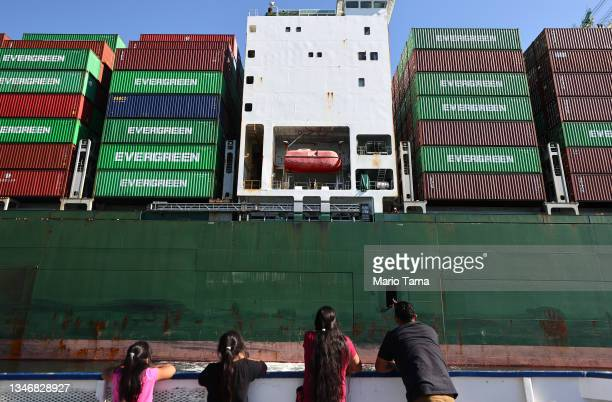 People ride on a tour boat beneath cargo containers stacked on a container ship at the Port of Los Angeles, the nation's busiest container port, on...