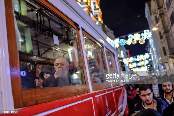 People ride on a tram in Istanbul as people prepare to celebrate the New Year in Istanbul on December 31 2017 Some of the 37000 police will be...