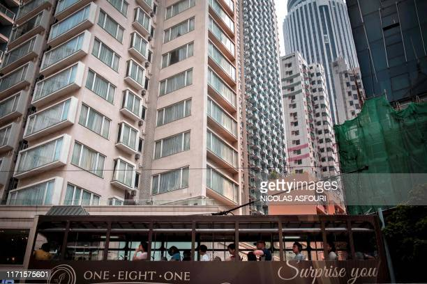 People ride on a tram past highrise residential buildings in the Wanchai district in Hong Kong on September 28 2019