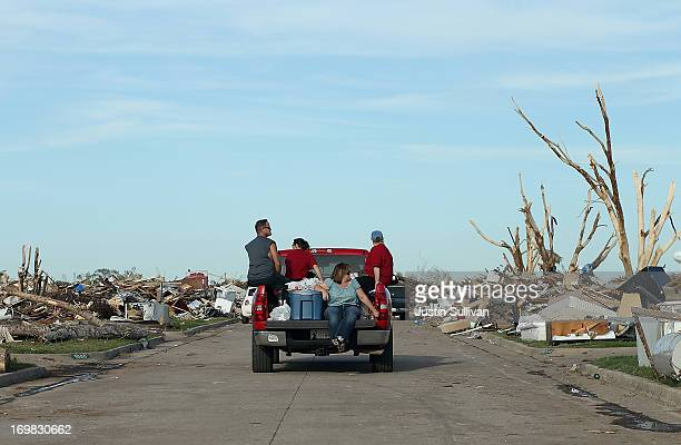 People ride on a truck through a neighborhood that was devastated by a tornado on June 2 2013 in Moore Oklahoma Residents of Moore Oklahoma continue...