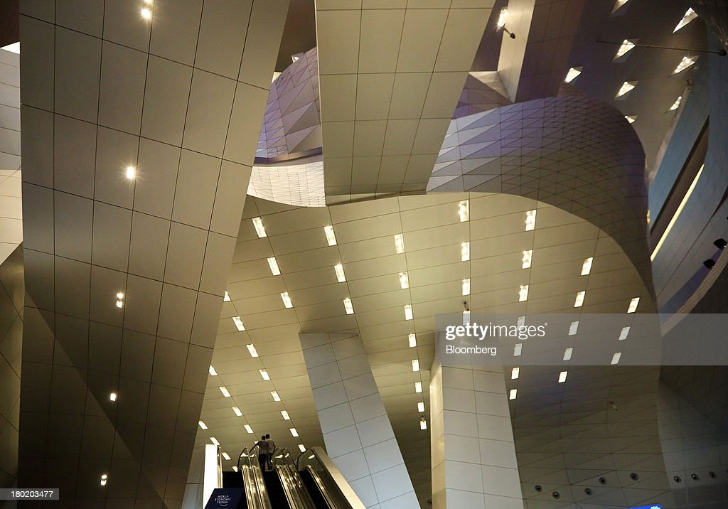 People ride on an escalator at the Dalian International Conference Center in Dalian, China, on Tuesday, Sept. 10, 2013. The World Economic Forum Annual Meeting Of The New Champions 2013 will be held in Dalian from Sept. 11 to 13. Photographer: Tomohiro Ohsumi/Bloomberg via Getty Images