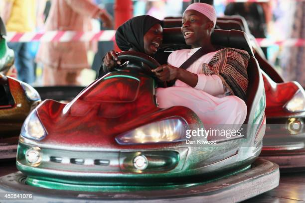 People ride on Bumper cars during an Eid celebration in Burgess Park on July 28 2014 in London England The Muslim holiday Eid marks the end of 30...