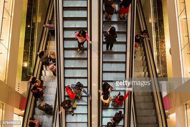 People ride on escalators in a shopping mall in Kuala Lumpur, Malaysia, on Tuesday, March 18, 2014. Malaysia, aspiring to become a developed nation...