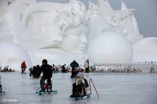 People ride on the ice in front of a snow sculpture in Harbin in China's northeastern Heilongjiang province on January 4 2019 / China OUT