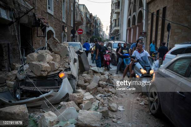 People ride past a car destroyed after a building wall collapsed after a large explosion on August 4, 2020 in Beirut, Lebanon. Video shared on social...