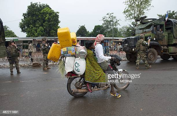 People ride past a checkpoint manned by French soldiers from the Sangaris operation in Bangui's PK-12 district on April 2, 2014. In the last few...