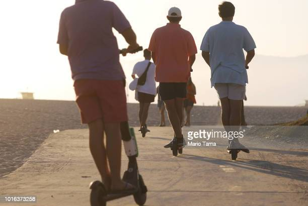 People ride shared dockless electric scooters along Venice Beach on August 13 2018 in Los Angeles California Some city residents complain the...