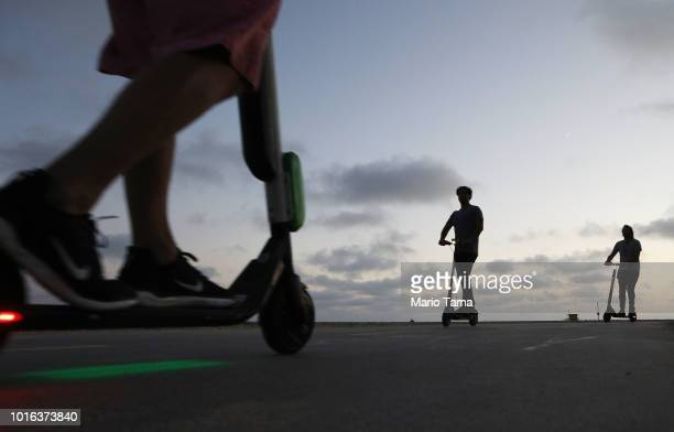 People ride shared dockless electric scooters along Venice Beach on August 13 2018 in Los Angeles California Shared escooter startups Bird and Lime...