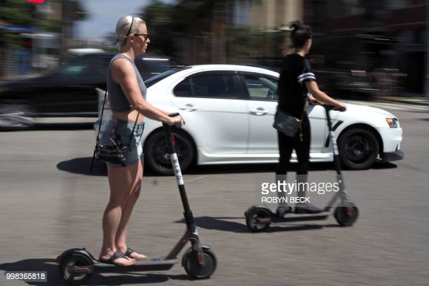 People ride shared electric scooters in Santa Monica California on July 13 2018 Cities across the US are grappling with the growing trend of electric...