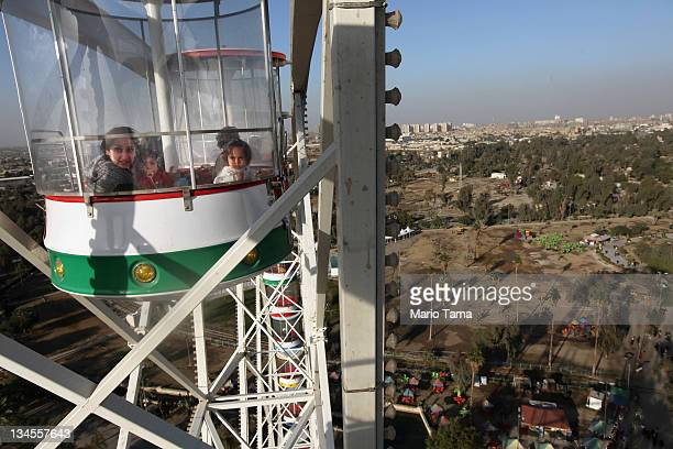People ride the Ferris wheel at Zawraa Park on December 2 2011 in Baghdad Iraq The 180foot tall Ferris wheel opened earlier this year and is the...