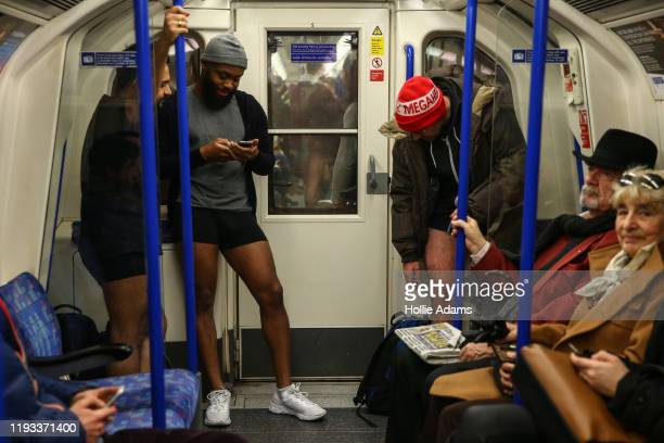 """People ride the Northern Line without trousers on January 12, 2020 in London, England. Originating as a prank on the New York Subway, the """"No Pants..."""