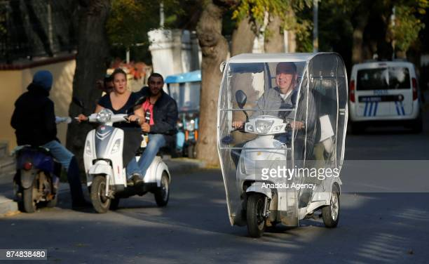 People ride their bicycles and electricpowered tricycles on an autumn day in Buyukada of Prince Islands of Istanbul Turkey on November 16 2017...