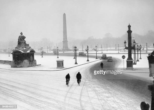 People ride their bicycles at the Place de la Concorde in Paris during the snowfalls on January28 1947