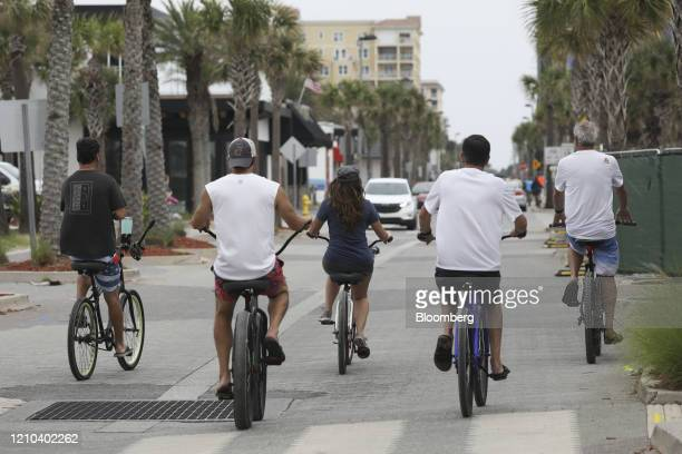 People ride their bicycles in Jacksonville Beach Florida US on Saturday April 18 2020 Florida reported a total of 25269 confirmed coronavirus cases...