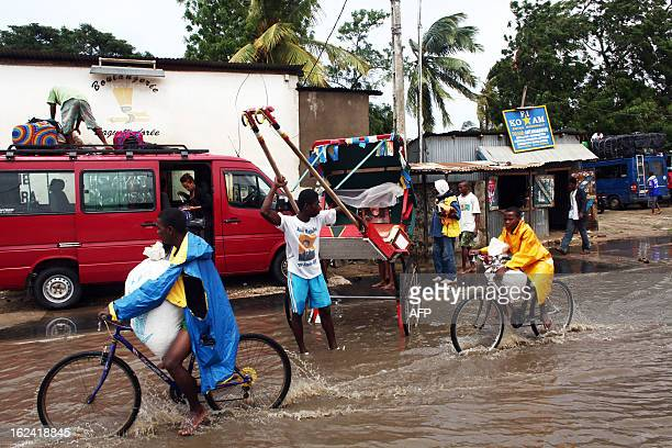 People ride their bicycles on a flooded street of Tulear Madagascar on February 23 a day after the cyclone Haruna hit the island AFP PHOTO / ANDREEA...