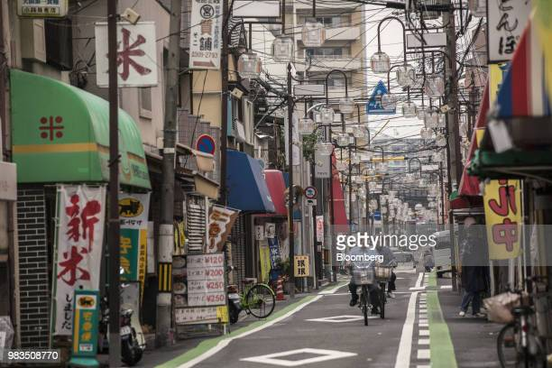 People ride their bicycles through a shopping district in Kadoma, Osaka Prefecture, Japan, on Friday, June 8, 2018. With anagingpopulation that...