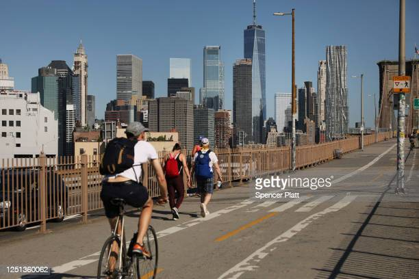 People ride their bikes across the Brooklyn Bridge as Manhattan enters Phase 2 of re-opening following restrictions imposed to curb the coronavirus...