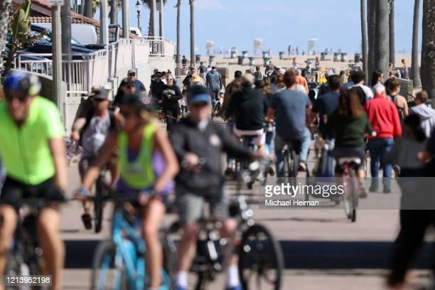 People ride their bikes along a bike bath near the pier on March 21 2020 in Huntington Beach California California Governor Gavin Newsom issued a...