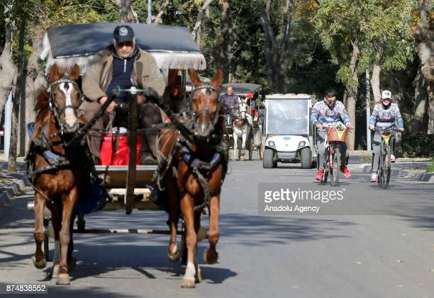 People ride their electricpowered tricycles as a phaeton passes near them on an autumn day in Buyukada of Prince Islands of Istanbul Turkey on...