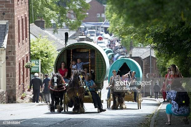 People ride their vardos or horsedrawn caravans along a road on the opening day of the annual Appleby Horse Fair in the town of ApplebyinWestmorland...