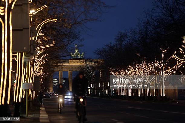 People Riding Bicycle On Street Amidst Illuminated Trees At Night
