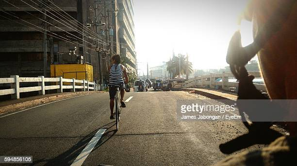People Riding Bicycle On Street During Sunny Day