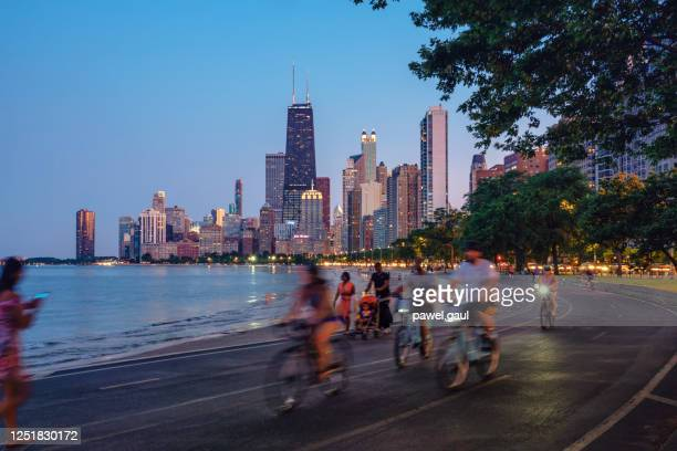 people riding bicycles at night with chicago skyline in background - waterfront stock pictures, royalty-free photos & images