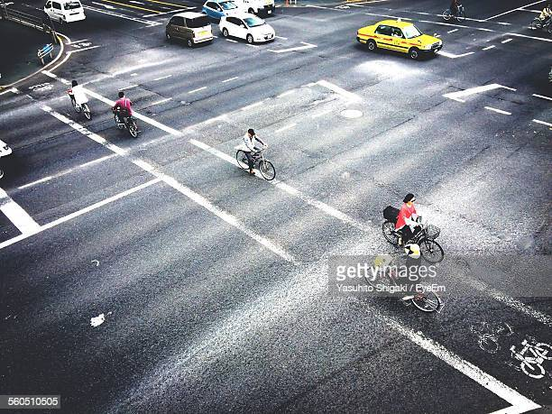 People Riding Bicycles On Crossroad