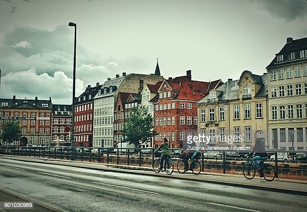 people riding bicycles on street by buildings against sky - zuzana janekova stock pictures, royalty-free photos & images