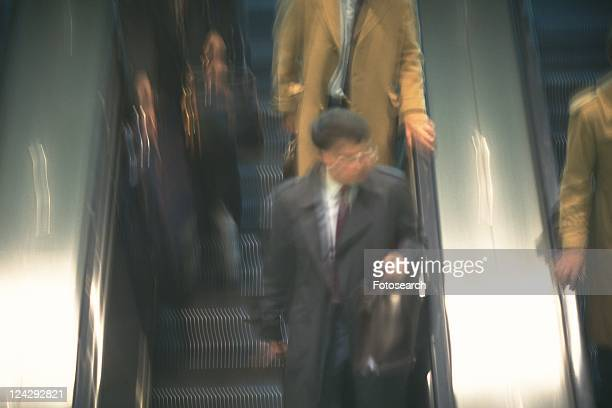 People riding escalators, high angle view, blurred motion, New York City, NY, USA