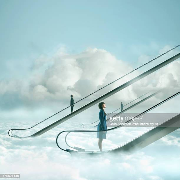 people riding escalators in sky - gleichheit stock-fotos und bilder