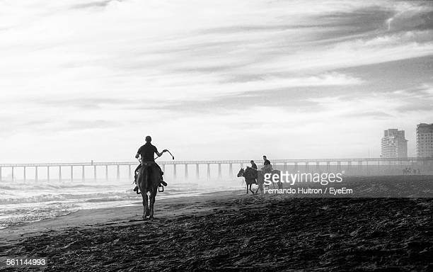people riding horses on beach - mexico black and white stock pictures, royalty-free photos & images