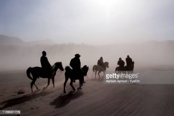 people riding horses on desert against sky - bromo tengger semeru national park stock pictures, royalty-free photos & images