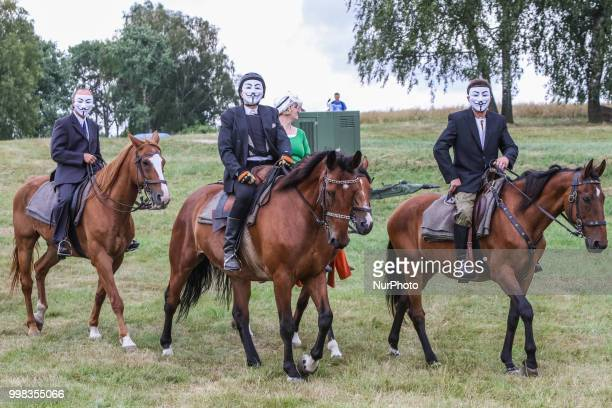 People riding horses wearing Guy Fawkes masks are seen in Grunwald Poland on 13 July 2018 Battle of Grunwald reenactment participants take part in...