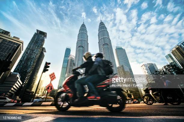 people riding motor cycle on road against buildings in city - petronas towers stock pictures, royalty-free photos & images