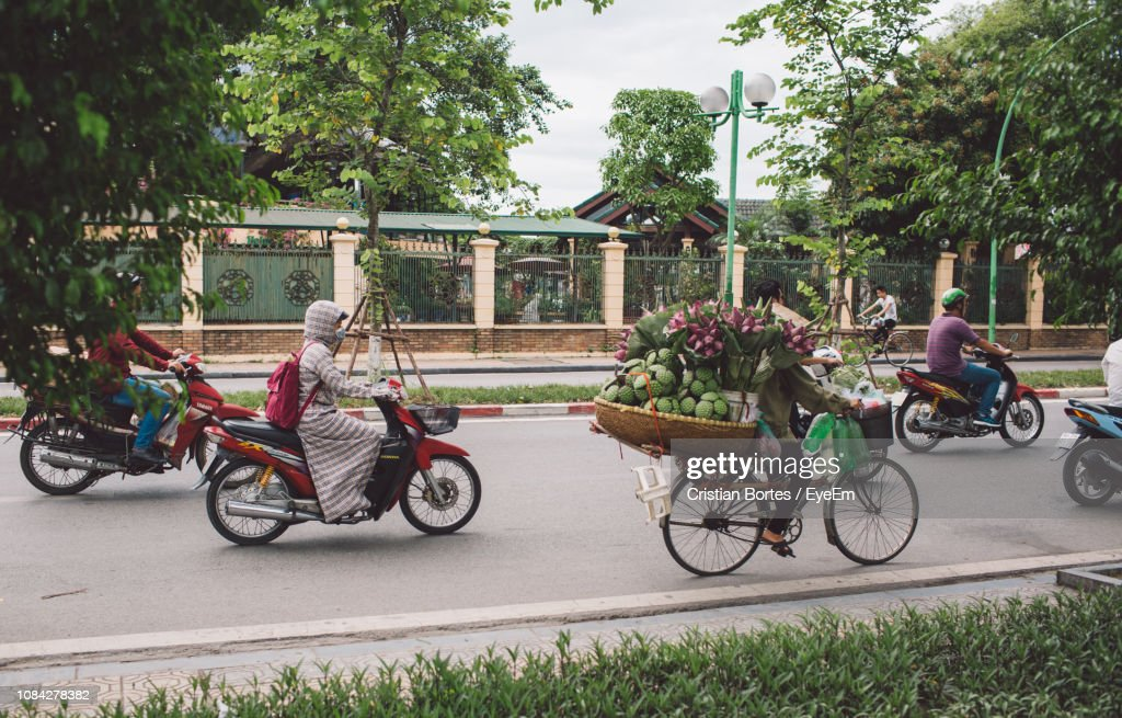 People Riding Motor Scooters On Road : Stock Photo