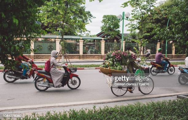 people riding motor scooters on road - bortes stock photos and pictures