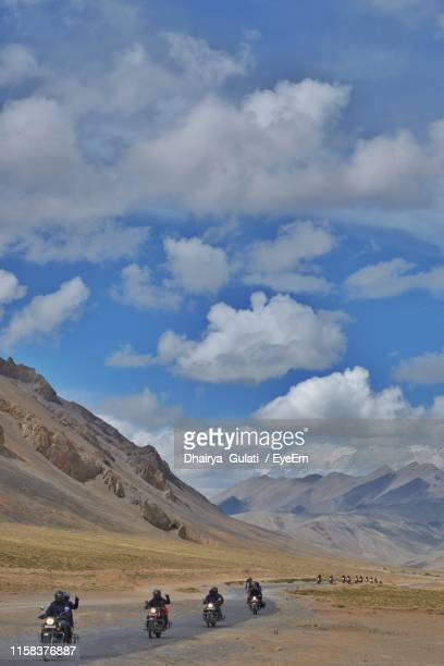 people riding motorcycles on road against cloudy sky - beauty in nature stock pictures, royalty-free photos & images