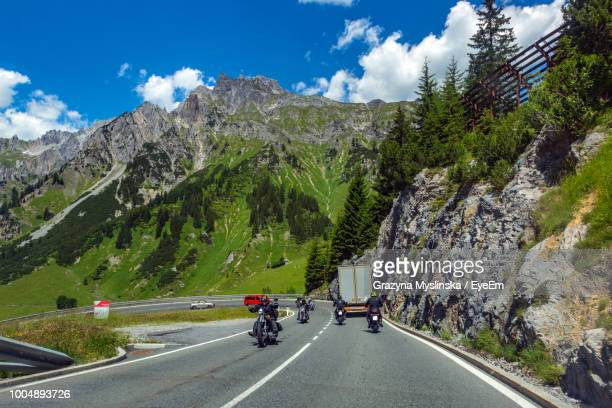 People Riding Motorcycles On Road Against Mountain