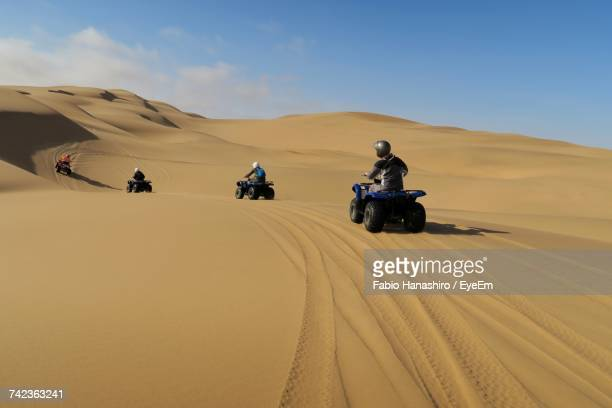 people riding off-road vehicles in the desert - sand dune stock pictures, royalty-free photos & images