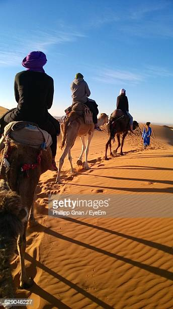 People Riding On Camels At Sahara Desert Against Sky