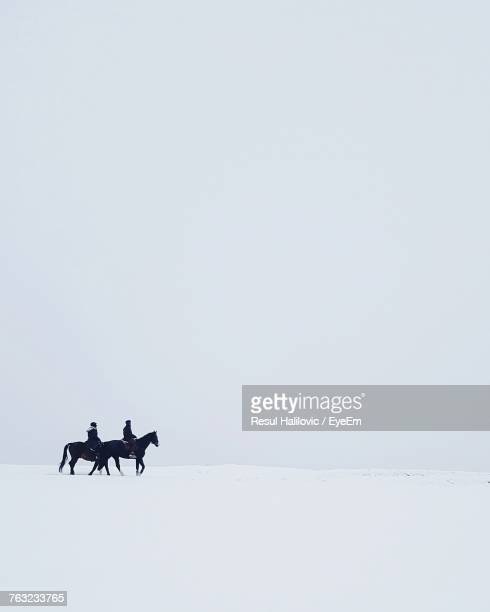 People Riding On Horses In Snow Against Clear Sky