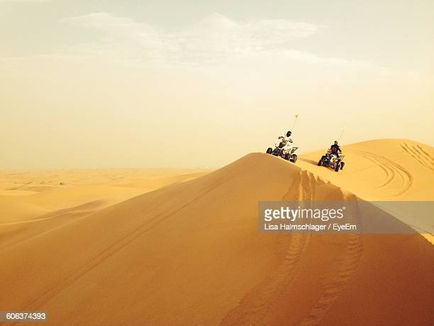 People Riding Quadbike On Sand Dune Against Sky