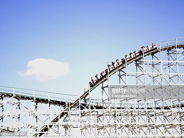 people riding rollercoaster, side view - high section stock pictures, royalty-free photos & images