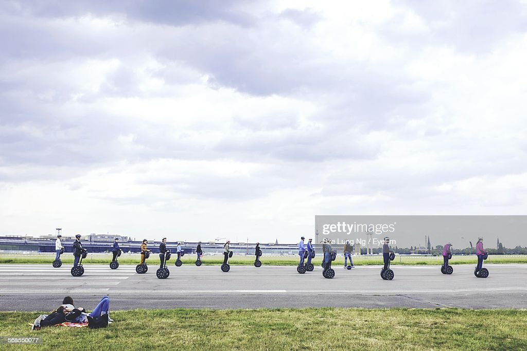 People Riding Segway On Road Against Cloudy Sky With Women Lying On Grass : Stock Photo