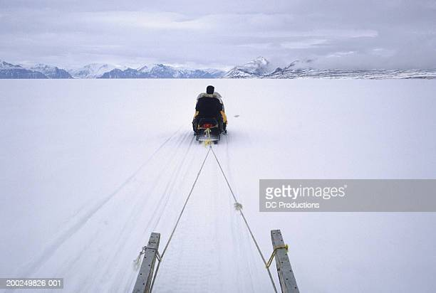 people riding snowmobile, baffin island, canada, elevated view, rear view - nunavut stock pictures, royalty-free photos & images