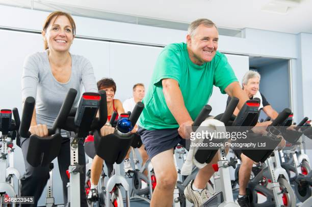 People riding spin bicycles in gym